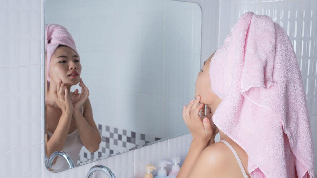 Frau vor dem Spiegel betrachtet ihre Haut